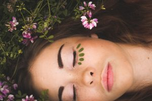 woman's face up close surrounded by leaves and flowers