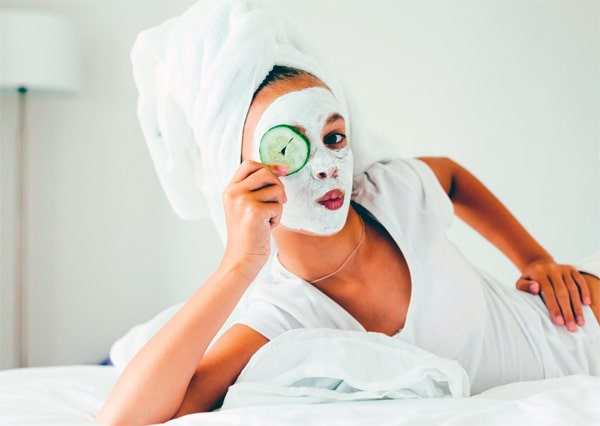 women having at home facial and laying on the bed
