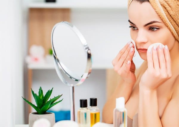 women removing makeup in front of the mirror